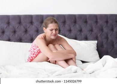 Young woman suffering from menstrual cramps at home. Gynecology