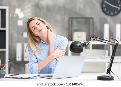 Young woman suffering from neck pain in office