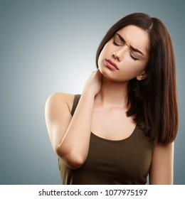 Young woman suffering from neck pain isolated on blue