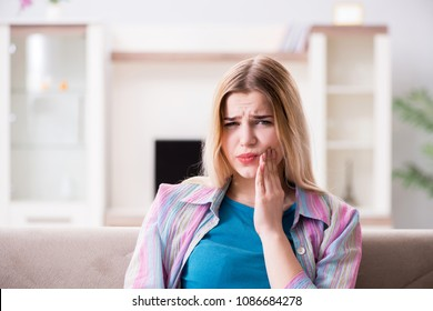 Young woman suffering with pain at home