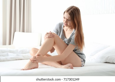 Young woman suffering from pain in leg at home