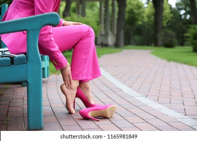 Young woman suffering from pain in legs because of uncomfortable shoes outdoors