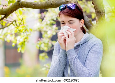 Young woman suffering from Pollen allergy, allergy season, Girl blowing her nose