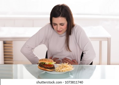 Young Woman Suffering From Stomach Pain While Having Breakfast