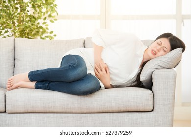 young woman suffering from stomachache on sofa at home. lifestyle and health concept. mixed race asian chinese model.