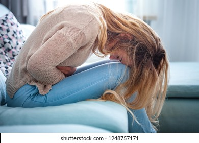 Young woman suffering from strong abdominal pain while sitting on sofa at home