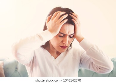 Young woman suffering from strong headache or migraine sitting at home, millennial guy feeling intoxication and pain touching aching head, morning after hangover concept