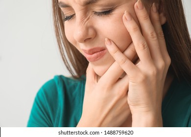 Young woman suffering from toothache against light background, closeup