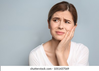 Young woman suffering from toothache on grey background