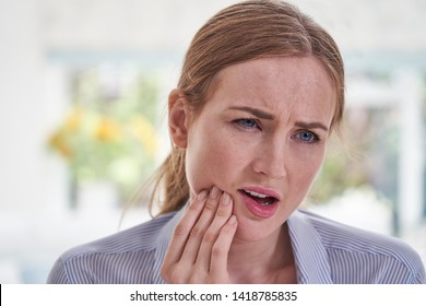 Young Woman Suffering With Toothache Touching Jaw