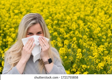 Young woman suffers from allergy in a rape field and has to sneeze
