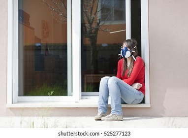 A young woman, suffers from MCS (Multiple Chemical Sensitivity) use the mask with carbon to breathe outside your home.