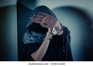 Young woman suffers from violence, covers her face with hands in handcuffs. Her