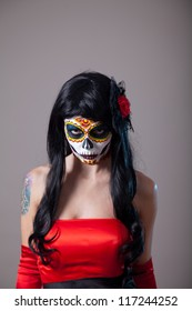 Young woman with sugar skull Halloween make-up wearing red dress, the Day of the Dead