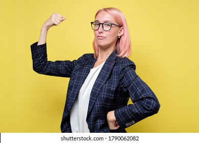 young woman in suit shows her muscles, strength and power concept, studio shoot isolated on yellow background