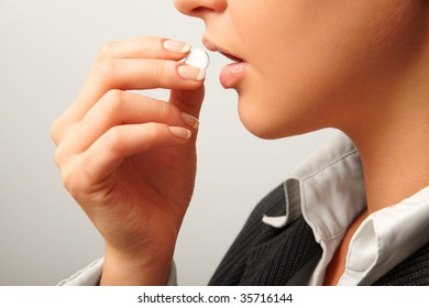 Young woman in suit taking white pill. Isolated on white. Closeup.