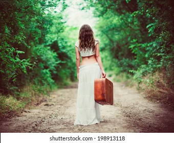 Young woman with suitcase in hand going away by a rural road