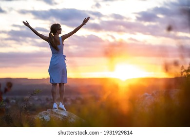 A young woman in summer dress raising up her hands standing outdoors enjoying view of bright yellow sunset.