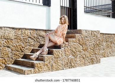 A young woman in a summer dress sits on the steps. Looks at the camera. On vacation
