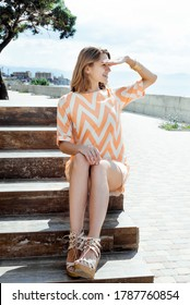 A young woman in a summer dress sits on the steps. Looks into the distance, into the future