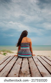 Young woman in summer dress sitting at the beach looking to a sky