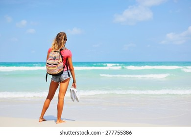 Young woman in summer dress standing by blue sea