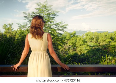 Young woman in summer dress standing at the terrace, looking at mountain. Back view.