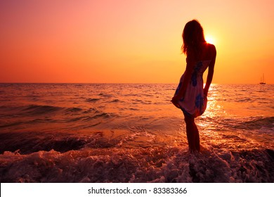 Young woman in summer dress standing on a rock and looking to a sea