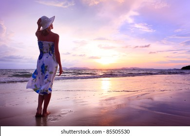 Young woman in summer dress standing on a sandy beach