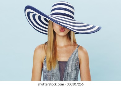 Young woman in sun hat blowing kiss