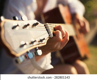 Young woman in sun park holding a guitar and playing music