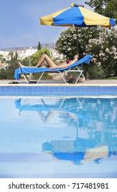 Young Woman Sunbathing In Bikini On Sunbed By Swimming Pool
