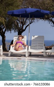 young woman sunbathing by the pool