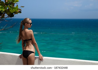 Young woman sunbathing. Luxury sea view.