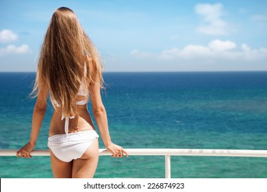 Young woman sunbathing. Nice sea view.
