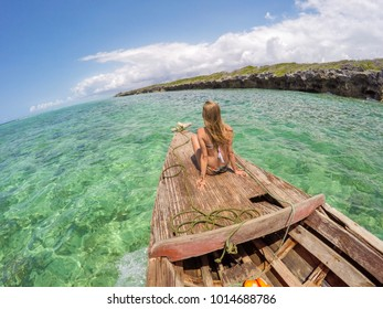 Young woman sunbathing on deck of old wooden boat