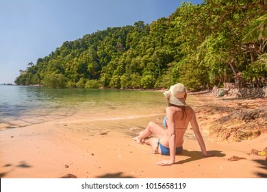 young woman sunbathing on a tropical beach in Thailand