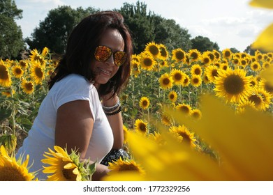 a young woman in a sunflower field with the relection of the flowers in her sunglasses