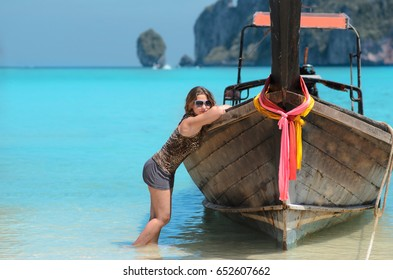 Young woman in sunglases near traditional longtail boat on Phi Phi islands, Thailand. Vacation concept