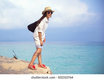 Young woman sunglass and hat smiling having fun standing in sea water