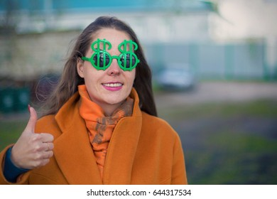 Young woman in sunglasses with dollar sign and OK gestures