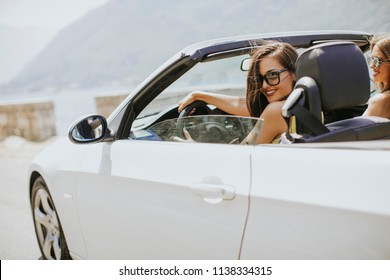 Young woman with sunglasses driving her convertible top automobile on bright sunny day near sea