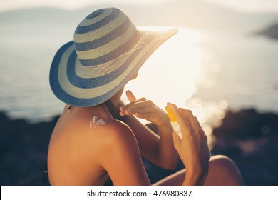 Young woman in sunglasses holding bottle of sunscreen lotion, spraying sunblock cream on shoulder before tanning