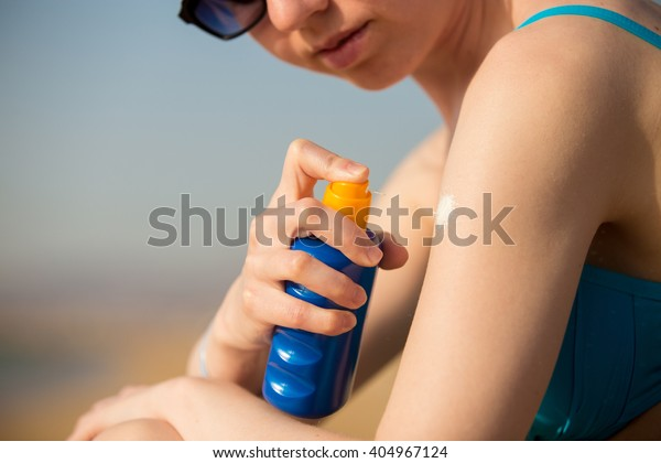 Young woman in sunglasses holding bottle of sunscreen lotion, spraying sunblock cream on shoulder before tanning, close up