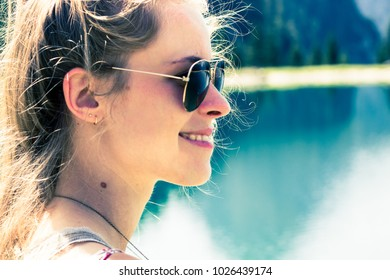 Young woman with sunglasses at a lake
