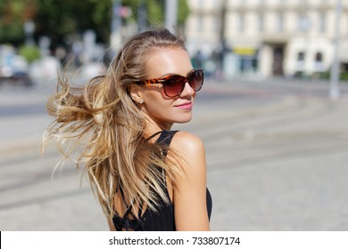 Young woman in sunglasses looking back portrait outdoor