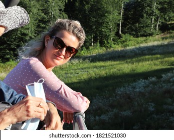 Young woman in sunglasses looks down at the hands of another woman with smile as she takes medical face mask from her bag. They are close to each other, watching the landscape