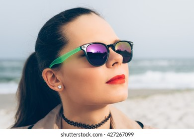Young woman in sunglasses looks at the sun on the beach in spring