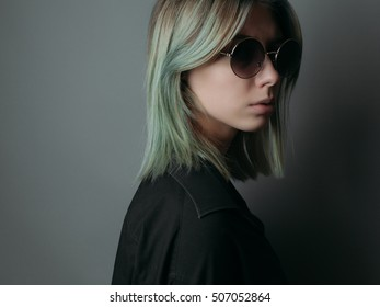 Young woman with sunglasses on grey background. Studio portrait