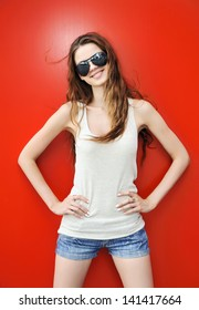 Young woman in sunglasses on red background